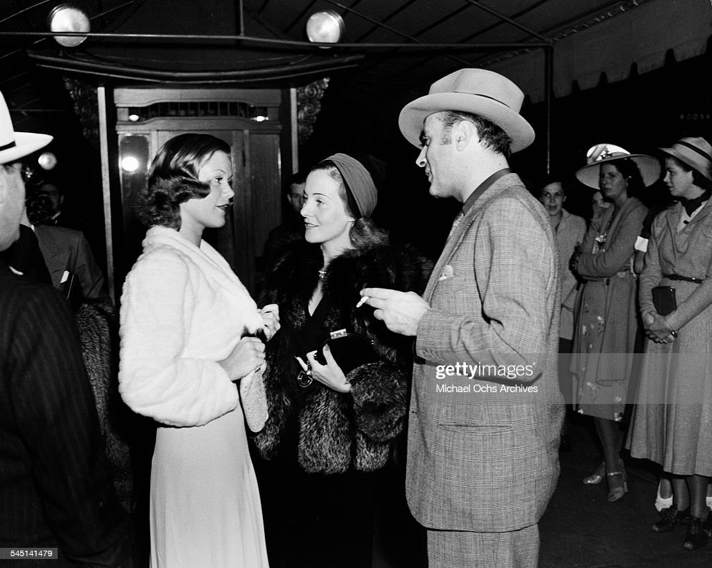 French actor Charles Boyer and wife Pat Paterson talks with French actress Simone Simon at an event in Los Angeles, California.