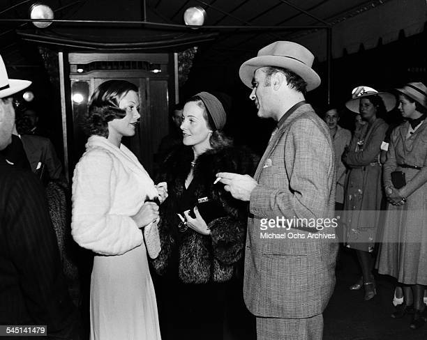French actor Charles Boyer and wife Pat Paterson talks with French actress Simone Simon at an event in Los Angeles California