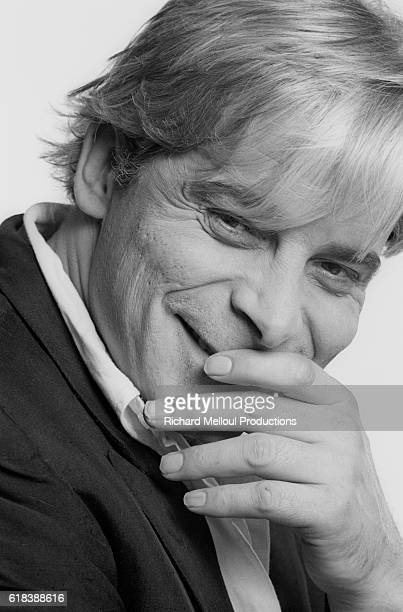 French actor, director, and screenwriter Jacques Weber puts his hand to his mouth as he laughs in Paris. In 1990, he is starring in a one-man show.