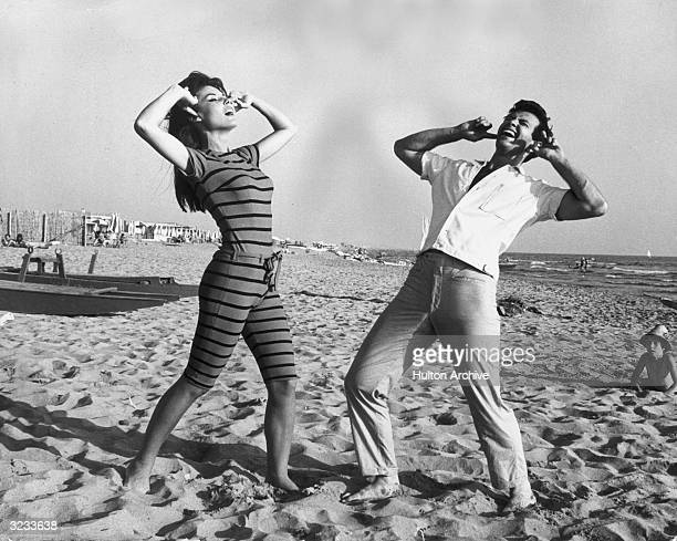 French actor Dominique Boschero and American actor Mark Damon demonstrate a dance called the 'HullyGully' on a beach