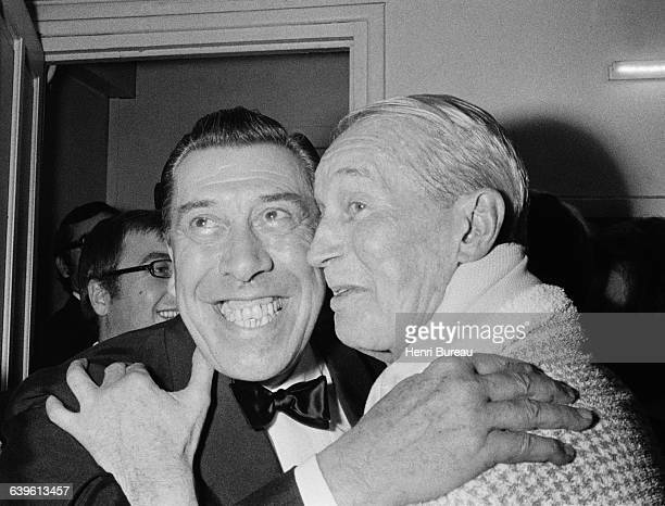 French actor Fernandel hugs singer Maurice Chevalier backstage during the singer's farewell concert for his public at the Theatre des ChampsElysees