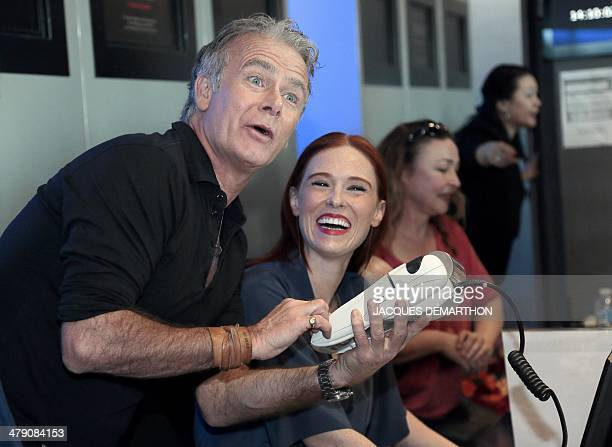 French actor Franck Dubosc flanked by French actress Audrey Fleurot jokes while holding a credit card reader during the launching of 'Le Printemps du...