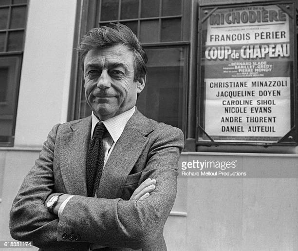 French actor Francois Perier stands near a poster advertising the play Coup de Chapeau Perier appears in the play directed by Pierre Mondy Other cast...