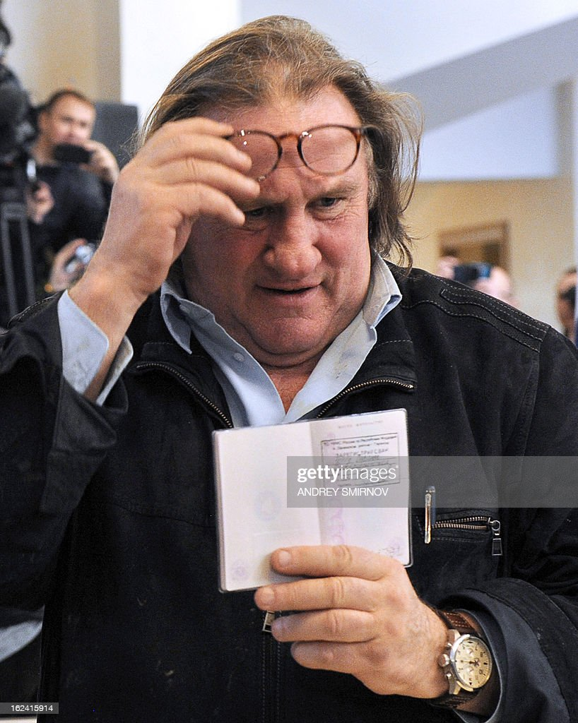 French actor Gerard Depardieu (C) holds his passport registration at the theatre in Saransk, on February 23, 2013. Depardieu, who was granted a Russian passport by President Vladimir Putin after complaining at high tax rates in France, was set to spend today in Moscow before travelling 650 kilometres (400 miles) to the provincial city of Saransk to register as a resident of No. 1 Democracy Street (Demokraticheskaya Ulitsa).