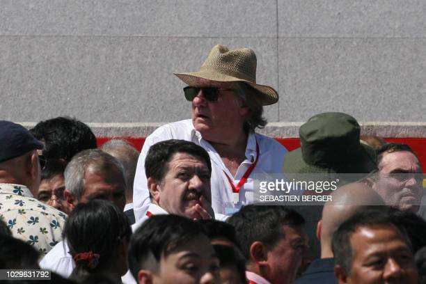 TOPSHOT French actor Gerard Depardieu looks on as he attends a military parade with an entourage including French writer Yann Moix and mass rally on...