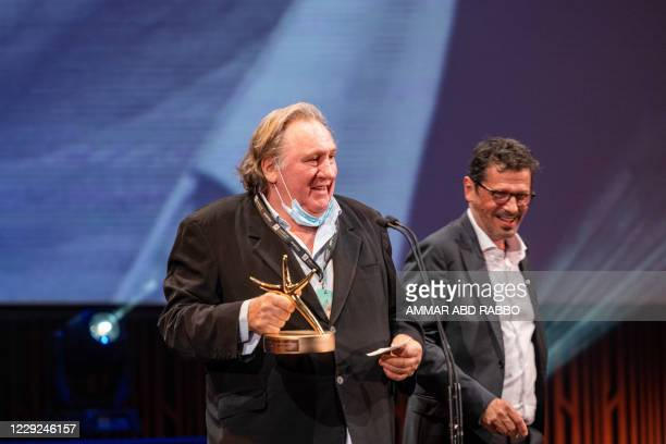 French actor Gerard Depardieu receives a career achievement award from producer Peter Webber during the opening ceremony of the 4th edition of El...
