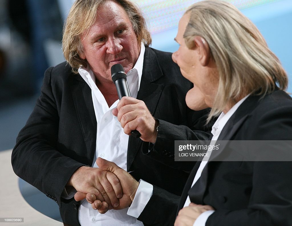 French actor Gerard Depardieu shakes hands with his puppet as he attends the Canal+ TV show 'Le Grand Journal' during the 63rd Cannes Film Festival on May 20, 2010 in Cannes.