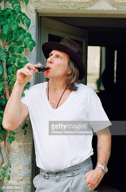 French actor Gerard Depardieu tasting a wine produced from his vineyard. | Location: Tigne, France.