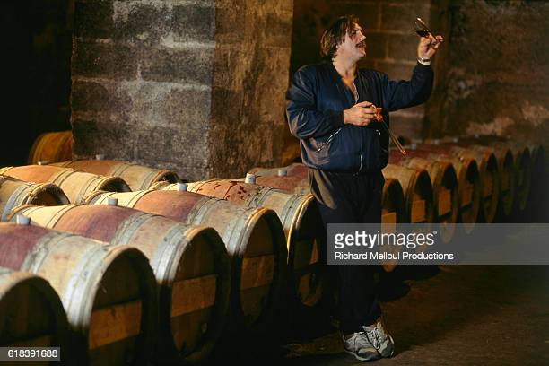 French actor Gerard Depardieu tasting his own wine from vineyard in his wine cellar | Location Tigne France