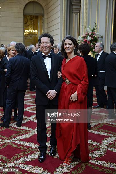 French actor Guillaume Gallienne and his wife Amandine Gallienne pose as they arrive at a state dinner at the Elysee presidential palace in Paris on...
