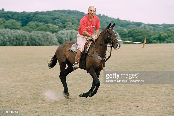 French actor Guy Marchand and owner of several polo horses, rides one of his polo ponies.