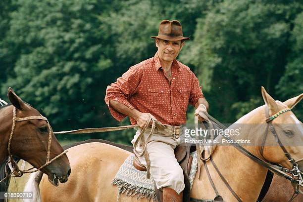 French actor Guy Marchand rides and leads his polo horses.
