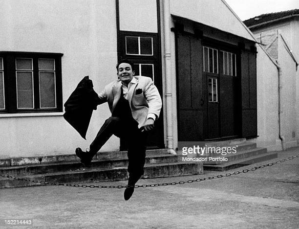 French actor Jacques Charrier jumping over a chain holding his jacket in his hand Paris 1959