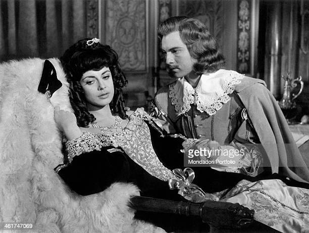French actor Jacques Toja holding by the hand Italian actress Anna Maria Ferrero lying on a chaise longue in the film Captain Fracasse France 1960