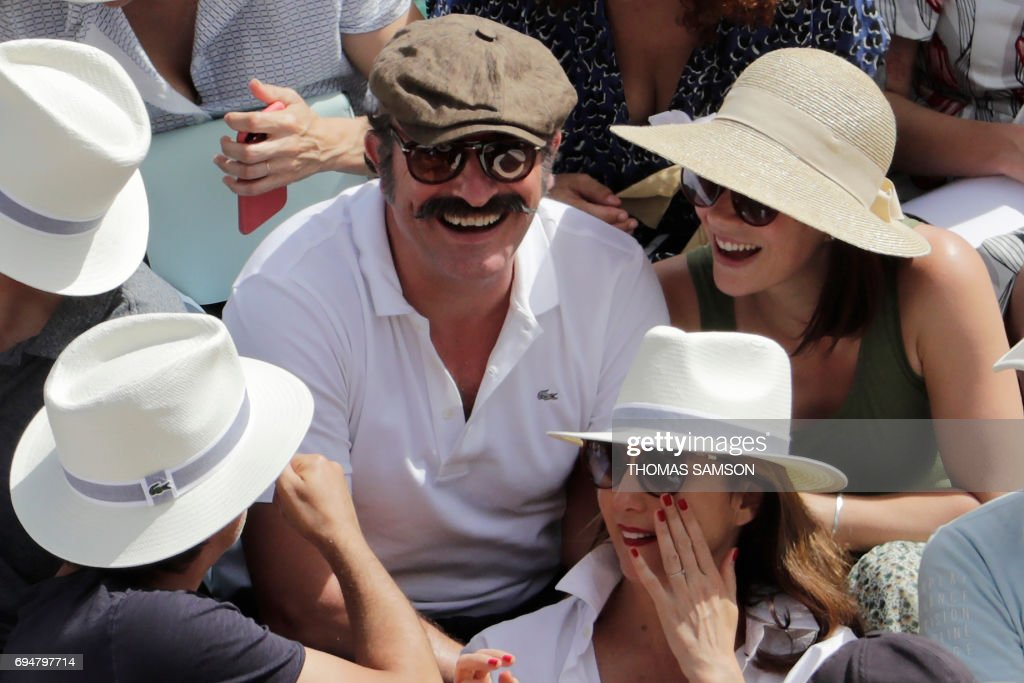 French actor Jean Dujardin (top-C) and his partner former French figure skater Nathalie Pechalat (topR), and French actress Elsa Zylberstein (R-bottom) attend the final tennis match between Spain's Rafael Nadal and Switzerland's Stanislas Wawrinka at the Roland Garros 2017 French Open on June 11, 2017 in Paris. / AFP PHOTO / Thomas SAMSON