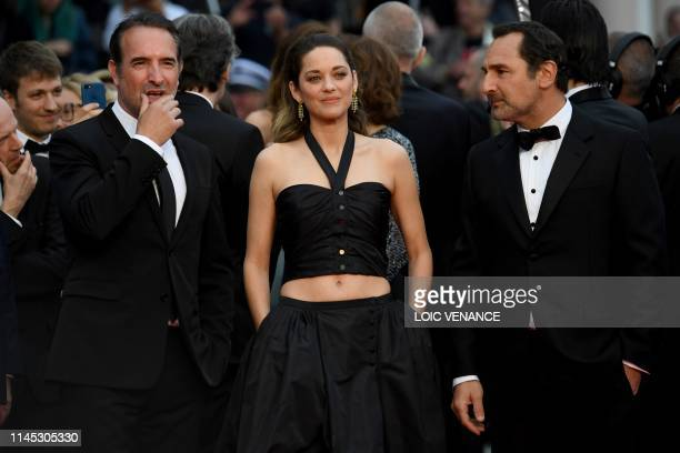 TOPSHOT French actor Jean Dujardin French actress Marion Cotillard and French actor Gilles Lellouche arrive for the screening of the film La Belle...