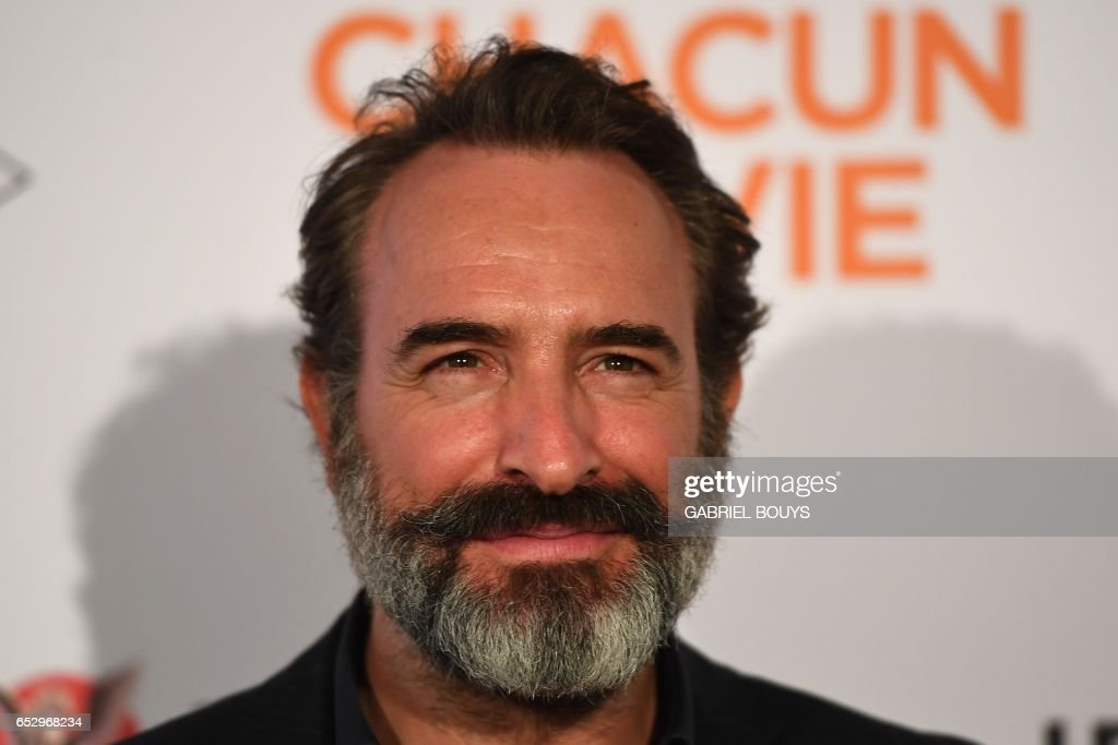 French actor Jean Dujardin poses during the photocall for the premiere of the film 'Chacun Sa Vie' in Paris on March 13, 2017. The film is directed by French director Claude Lelouch. /