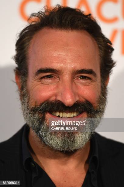 French actor Jean Dujardin poses during the photocall for the premiere of the film 'Chacun Sa Vie' in Paris on March 13 2017 The film is directed by...