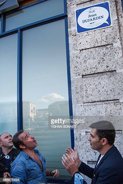 French actor Jean Dujardin reacts during the inauguration of a street to be temporarily named 'Rue Jean Dujardin' flanked by Mayor of Angouleme...