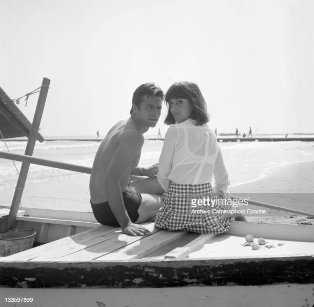 French actor Jean Sorel with his wife Anna Maria Ferrero sitting on a boat on the seashore portrayed from the back Lido Venice 1967