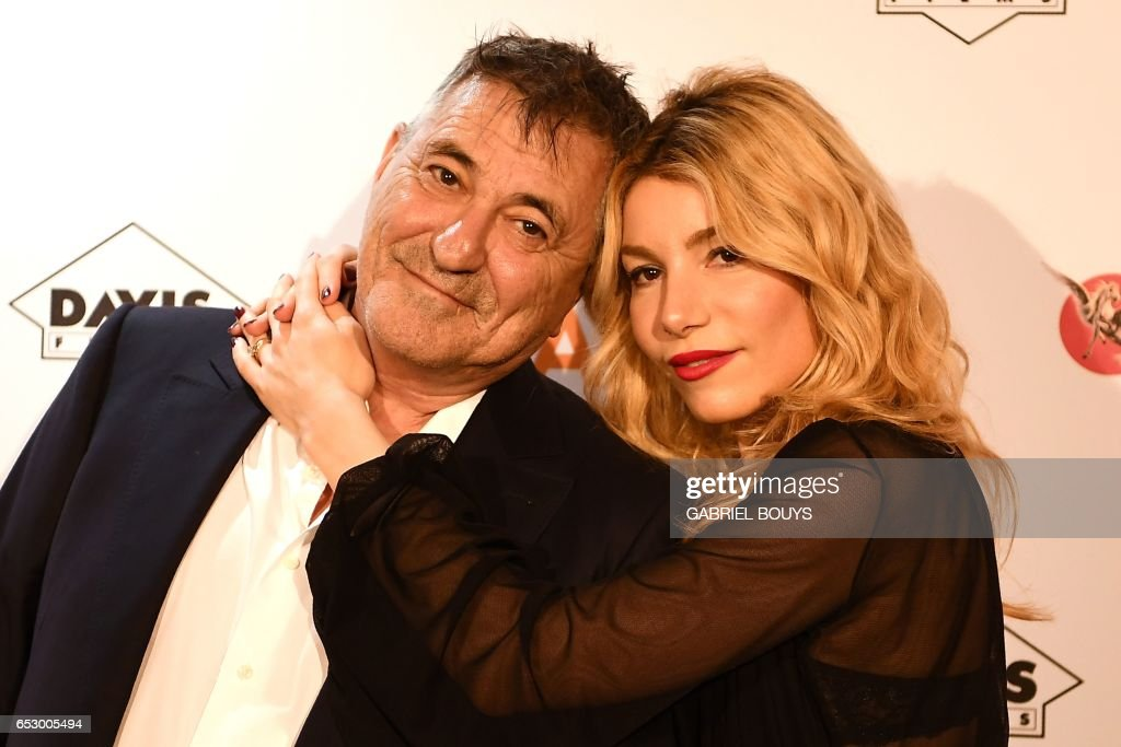 French actor Jean-Marie Bigard poses with his wife Lola Marois during the photocall for the premiere of the film 'Chacun Sa Vie' in Paris on March 13, 2017. The film is directed by French director ...