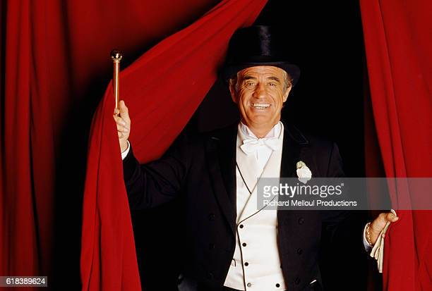 French actor Jean-Paul Belmondo emerges from a curtain dressed in a tuxedo for his role in the Georges Feydeau play Tailleur pour les Dames.
