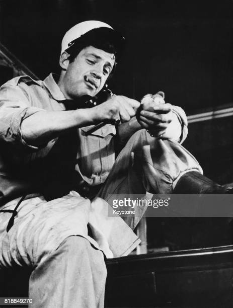 French actor JeanPaul Belmondo peeling potatoes in his role as a French Foreign Legionary in the film 'Dragées au poivre' directed by Jacques...