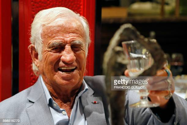 French actor JeanPaul Belmondo raises his glass after being awarded of the 'Prix du singe' in reference to the movie 'Un Singe en Hiver' and in...