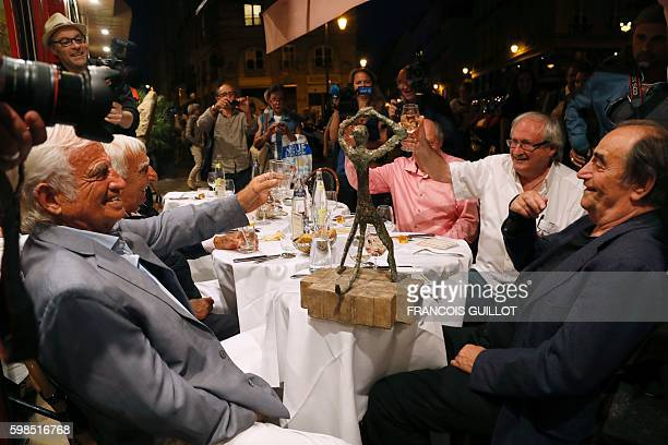 French actor Jean-Paul Belmondo raises his glass next to French actor Charles Gerard and French and Senegalese actor Richard Bohringer after being...