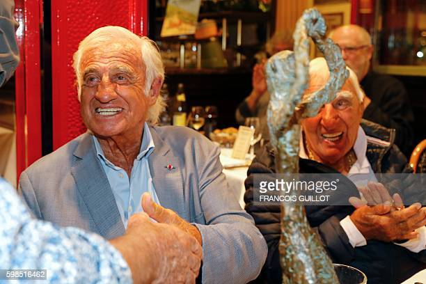French actor JeanPaul Belmondo smiles as he shakes hands next to French actor Charles Gerard after being awarded of the Prix du singe in reference to...