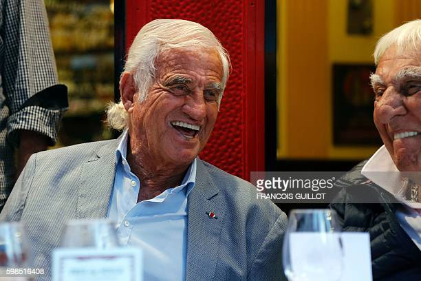 French actor JeanPaul Belmondo smiles next to French actor Charles Gerard after being awarded of the 'Prix du singe' in reference to the movie 'Un...