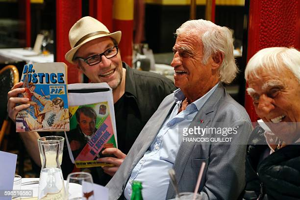 French actor JeanPaul Belmondo smiles next to French actor Charles Gerard and a man holding vintages magazine spicturing Belmondo on cover after...