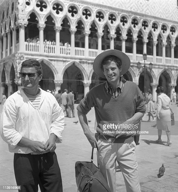 French actor JeanPaul Belmondo wearing a straw hat a striped shirt and holding sunglasses standing in St Mark Square in front of Doge's Palace next...