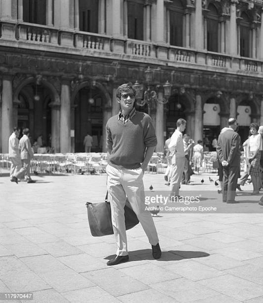 French actor JeanPaul Belmondo wearing a striped shirt a sweater and sunglasses holding a bag and standing in St Mark's Square Venice 1960