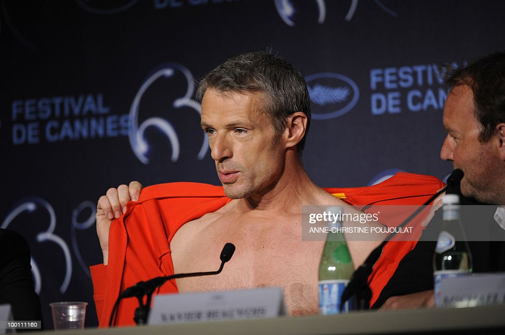 French actor Lambert Wilson opens his sweater as he speaks during the press conference of 'Des Hommes et des Dieux' (Of God and Men) presented in competition at the 63rd Cannes Film Festival on May 18, 2010 in Cannes.