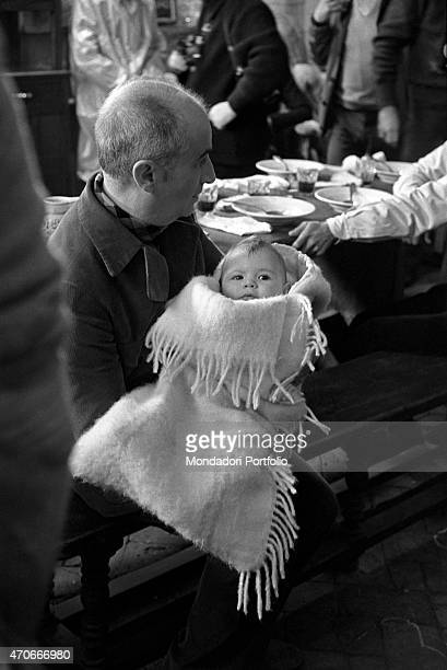French actor Louis de Funs born Louis Germain David de Funs de Galarza is seated on a bench and holds a cute newborn baby in his arms on the set of...