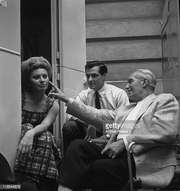 French actor Maurice Chevalier touches the face of Italian actress Sophia Loren as John Gavin watches on the set of the Michael Curtiz film 'A Breath...