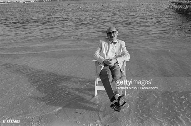 French actor Michel Blanc sits on a chair surrounded on a beach during Cannes' 36th film festival.