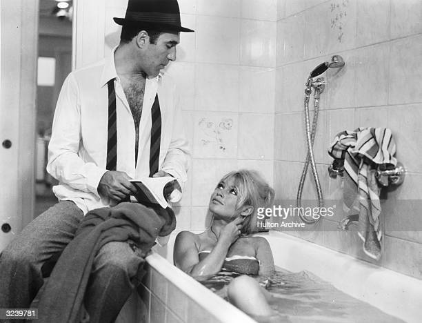French actor Michel Piccoli sits on the edge of a tub while French actor Brigitte Bardot takes a bath in a still from director JeanLuc Godard's film...