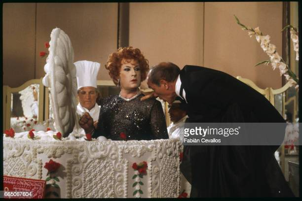 French actor Michel Serrault dressed as transvestite comes out of a giant cake with French actor Marcel Bozzuffi in a tuxedo on the set of French...