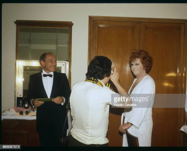 French actor Michel Serrault poses for a photographer as a transvestite with french actor Marcel Bozzuffi in tuxedo on the set of french director...