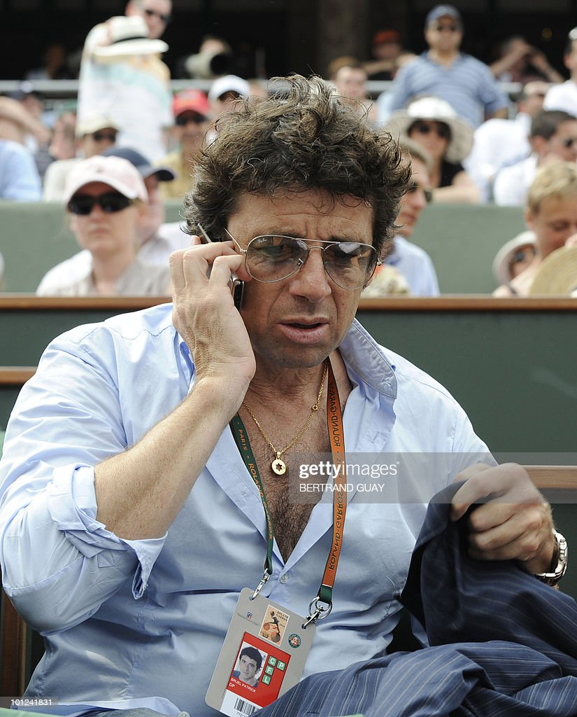 French actor Patrick Bruel speaks on his mobile phone as he watches the action during the the French Open tennis championship at the Roland Garros stadium, on May 25, 2010, in Paris.