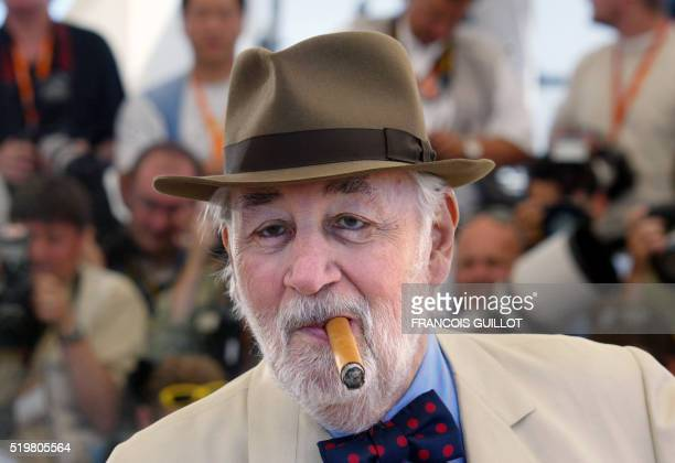 French actor Philippe Noiret smokes a cigar as he poses for photographers on a terrace of the palais des festivals during the photocall for the film...