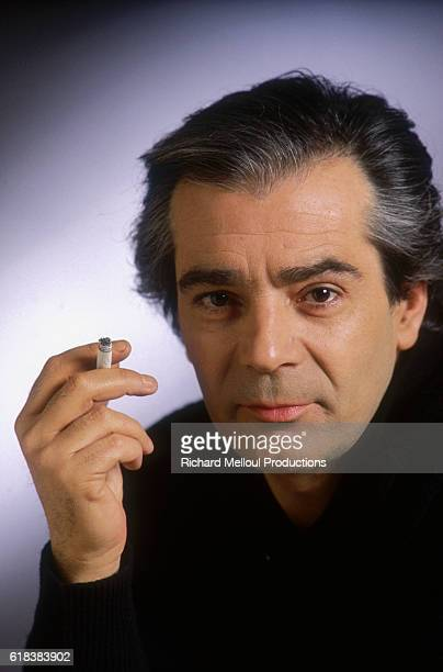 French actor Pierre Arditi holds a cigarette between his fingers
