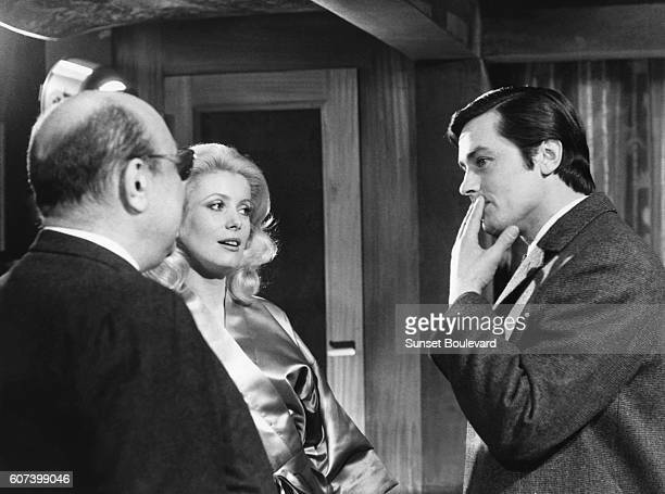 French actors Catherine Deneuve and Alain Delon and director and screenwriter JeanPierre Melville on the set of Melville's movie Un Flic