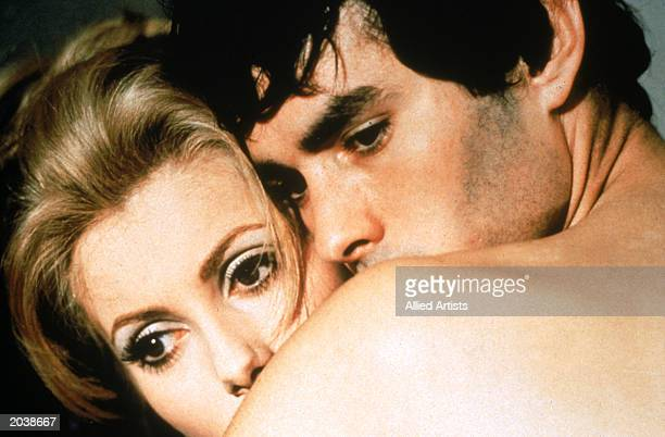 French actors Catherine Deneuve and Pierre Clementi embracing in a scene from the film 'Belle de Jour' directed by Luis Bunuel 1967