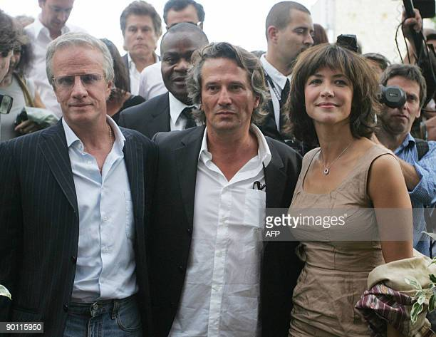 French actors Christophe Lambert and Sophie Marceau pose with French director Alain Monne as they present their movie L'homme de Chevet on August 27...