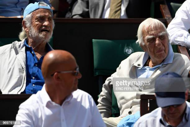 French actors JeanPaul Belmondo and Charles Gerard look on as Austria's Dominic Thiem plays Italy's Marco Cecchinato during their men's singles...