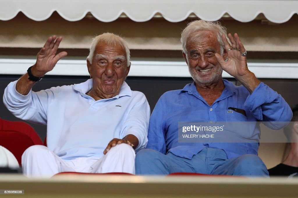 TOPSHOT - French actors Jean-Paul Belmondo (R) and Charles Gerard (L) wave as they attend the French football match Monaco vs Toulouse, on August 4, 2017 at the 'Louis II Stadium' in Monaco. /