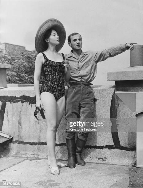 French actors Leslie Caron and Charles Aznavour enjoy the sun on a rooftop in Paris France during the filming of 'Les deux Pigeons' René Clair's...